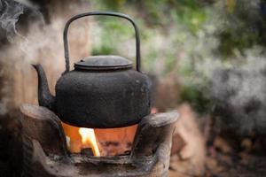 Kochen Sie Wasser alter Wasserkocher auf dem Feuer mit einem Holzkohleofen auf unscharfem Hintergrund foto
