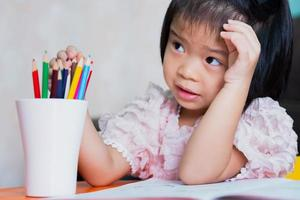 Mädchen saß und hörte zu, wie die Erwachsenen ihre Hausaufgaben machten, und sie spielte die Holzfarbe im weißen Glas. Kinder waren von den Anweisungen verwirrt. foto