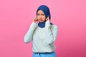 Porträt einer wütenden jungen Asiatin, die ihre Ohren mit dem Finger bedeckt foto