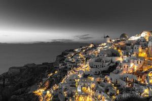 selektives Farbbild, orange Farbe mit Schwarz-Weiß-Prozess. Nachtlichter über dem Dorf Oia in Santorini, Griechenland. berühmtes Reiseziel, künstlerische Kunstvorlage. Entspannen, Stadtbild inspirieren foto