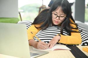 Teenager Studentin schlafen auf Kissen Buch lesen und Laptop verwenden. Sie schreibt Notizen, um sich auf die Prüfung vorzubereiten. foto