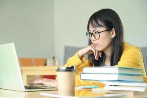 Kaffeetassen und Notebook auf dem Tisch mit Studentin im Teenageralter verwenden Laptop auf der Rückseite. foto