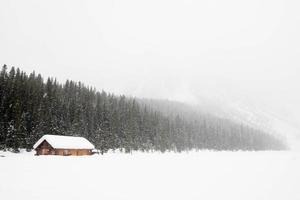 schöne Winterlandschaft mit Schnee. ein Holzhaus in der Nähe eines Waldes während eines schweren Schneesturms. Banff-Nationalpark, Kanada. foto