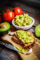 Guacamaole mit Brot und Avocado auf rustikalem hölzernem Hintergrund