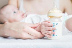 Baby hält eine Babyflasche mit Muttermilch foto