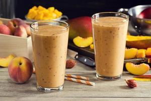 zwei Pfirsich-Mango-Smoothies in Gläsern mit Zutaten