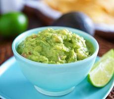 Guacamole in bunter blauer Schüssel mit Tortillachips foto