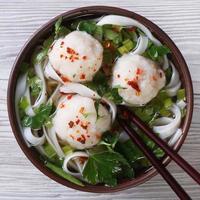 traditionelle Suppe mit Fischbällchen und Reisnudeln Nahaufnahme.