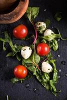 frischer Tomaten-Mozzarella-Salat auf schwarzem Schiefer foto