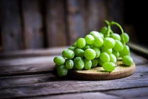 Weinrebe der grünen Trauben auf rustikalem hölzernem Hintergrund