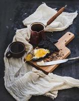 Frühstücksset. Kaffee, schwarzer Toast mit Frischkäse und Orange