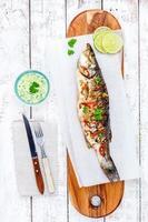 gebackener Fisch Wolfsbarsch mit Limette und Petersilie foto