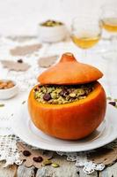 Kürbis gefüllt mit Hirse, Spinat, getrockneten Preiselbeeren, Pilzen und Mandeln foto