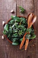 grüne Blattmischung über rustikalem hölzernem Hintergrund foto