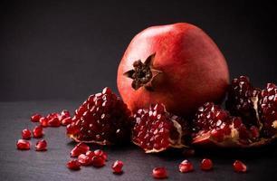 einige rote Granatäpfel auf schwarzer Schieferplatte foto