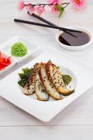geräucherter Aalsashimi auf einem weißen Teller über hölzernem Hintergrund foto