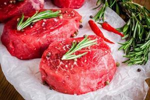 zwei rohe Steaks mit Rosmarin, Knoblauch, Salz und Pfeffer foto