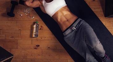 Frau mit muskulösen Bauchmuskeln, die auf Yogamatte im Fitnessstudio liegen foto