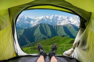 Blick aus einem Zelt auf die schneebedeckten Berge