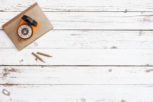 leerer Holztisch mit Bastel-Grunge-Notizbuch und Kompass