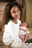 Afroamerikanerkind, das winziges neugeborenes Baby hält foto