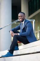 freundlicher junger Geschäftsmann, der auf Stufen in der Stadt sitzt foto
