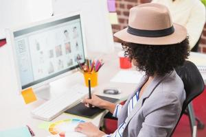 weiblicher Bildbearbeiter mit Digitalisierer im Büro