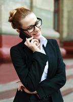 lächelnde Geschäftsfrau, die auf Handy spricht
