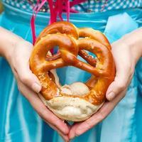 glückliche schöne frau im dirndlkleid mit oktoberfest pretz