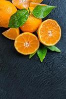 frische Mandarine auf schwarzem Stein