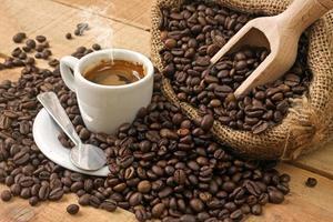 Kaffeetasse und Körner auf Holztisch