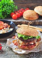hausgemachtes Burger-Rindfleisch mit gebratenen Zwiebeln auf einem hölzernen Hintergrund foto