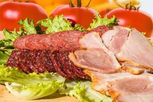 Stücke geräucherten Salams und Schinkens mit Salat schneiden foto