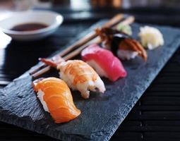 Nahaufnahme oder verschiedene Sushi Nigiri auf schwarzem Schiefer foto
