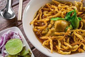 Curry-Nudelsuppe, umgeben von frischen Zwiebeln und Limetten