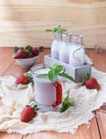 Erdbeermilchshake auf einem rustikalen Holztisch foto