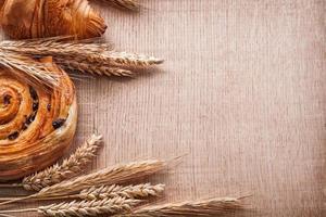 goldene Weizenohren süße Croissantrolle mit Rosinen auf Eiche foto