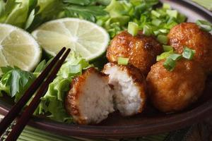 Fischbällchen mit Limette und Salat auf Teller Makro. horizontal
