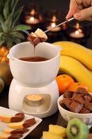 Schokoladenfondue-Tasse mit Kerzen und verschiedenen Früchten foto