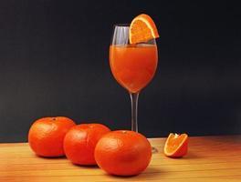 Orangensaftglas mit Orangen
