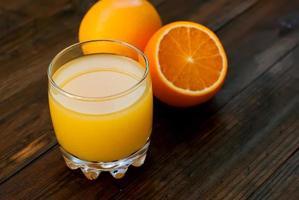 frischer Orangensaft auf Holztisch foto