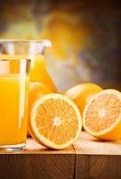Orangen und Saft in Glas schneiden foto
