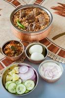 indisches Hammel (Lamm) Biryani / Briyani mit traditionellen Seiten foto