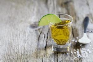 Tequila Schuss mit Limette und Meersalz auf rustikalem Brett
