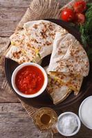 Quesadilla in Scheiben geschnitten und Saucen auf Teller Nahaufnahme. Vertikale foto