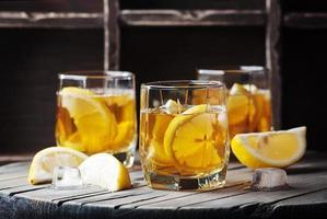 kalter Whisky mit Eis und Zitrone auf dem Vintage Tisch foto