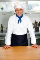hübscher junger Koch, der in Uniform aufwirft foto