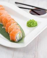 Lachssushi-Rolle auf einem weißen Teller mit Wasabi