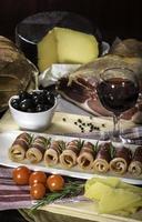 Parmaschinken, schwarze Oliven, Manchego-Käse und Brottisch foto