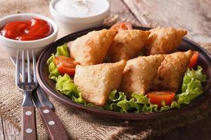 Samosa leckeres Gebäck auf einem Teller mit Tomaten und Salat foto